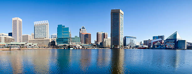 Baltimore Inner Harbor With Reflections in Early Morning - Panorama Panorama of Baltimore's Inner Harbor with numerous skyscrapers casting a reflection in the early morning sunshine. inner harbor baltimore stock pictures, royalty-free photos & images
