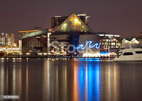 Baltimore's Inner Harbor cityscape at night with low clouds. The National Aquarium is aglow casting beautiful reflections on the calm water of the harbor.