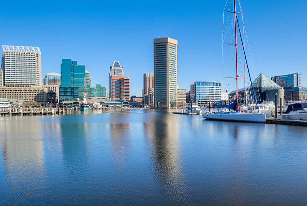Baltimore's Inner Harbor Buildings and Sailboat With Clear Blue Sky The clear blue sky and buildings along Baltimore's Inner Harbor are reflected in the water in the early morning sunshine. inner harbor baltimore stock pictures, royalty-free photos & images