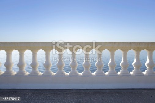 A beautiful balustrade basked in early morning sun with the sea visible beyond.