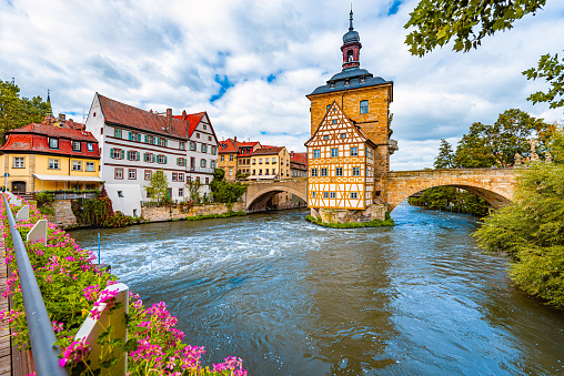 Bamberg city in Germany. Town hall building in background with blue cloudy sky.  Architecture and travel in Europe. Flowing river in foreground.
