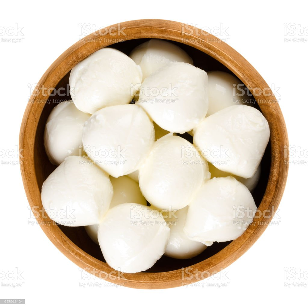 Bambini mozzarella in wooden bowl over white stock photo
