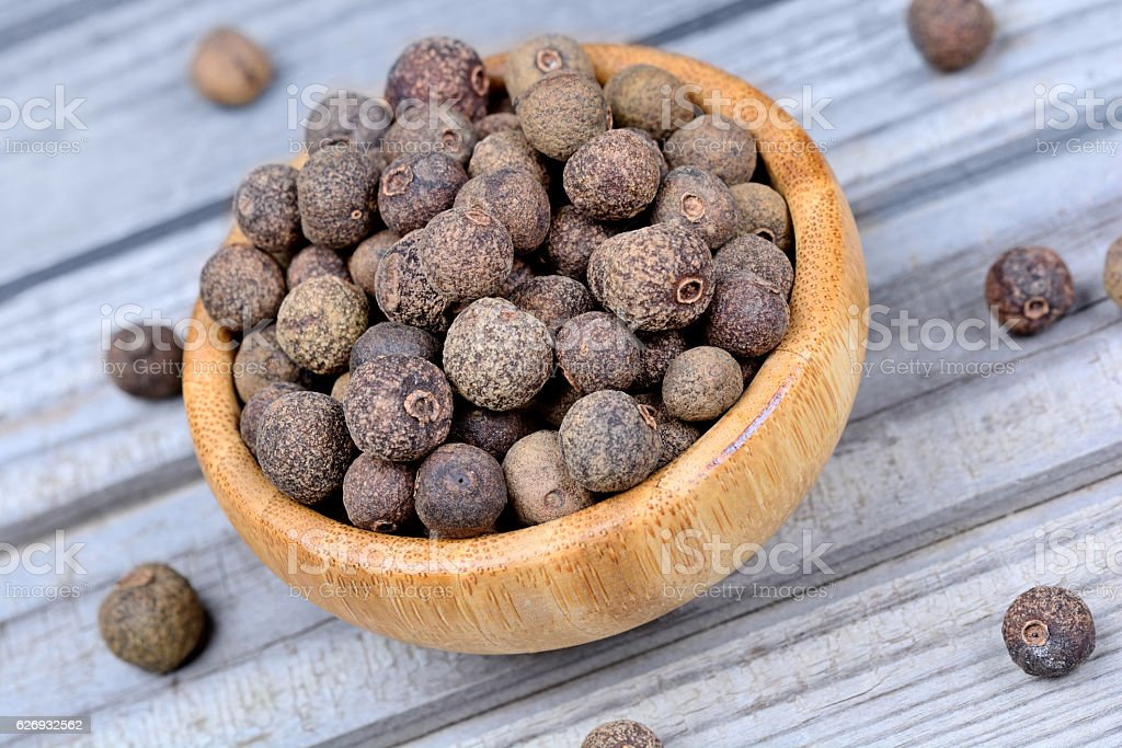 Bamboo bowl with allspice on table stock photo