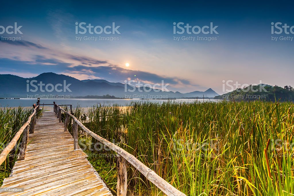 Bamboo bridge near reservoir with mountain and sky view stock photo