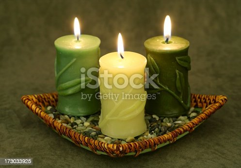 Trio of burning candles embossed with bamboo leaves, in basket with pebbles. Horizontal image.