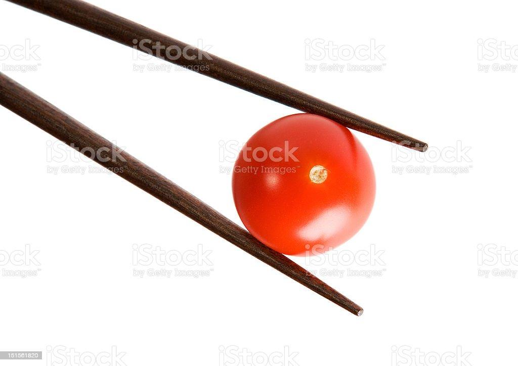 Bamboo chopsticks and cherry tomato on white background royalty-free stock photo