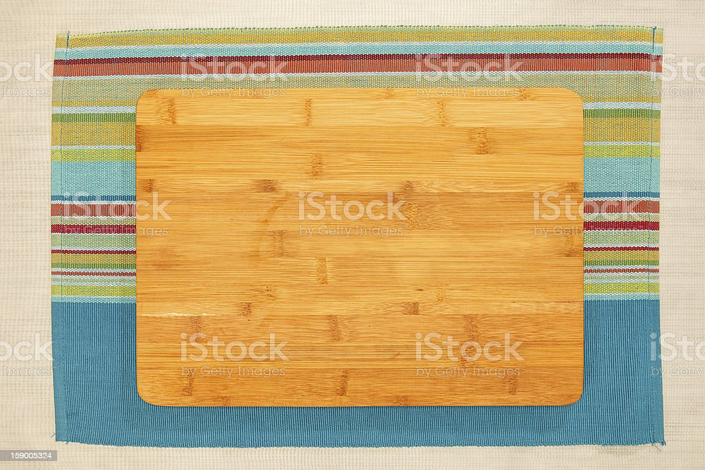 Bamboo cutting board on a colored striped mexican tablecloth stock photo