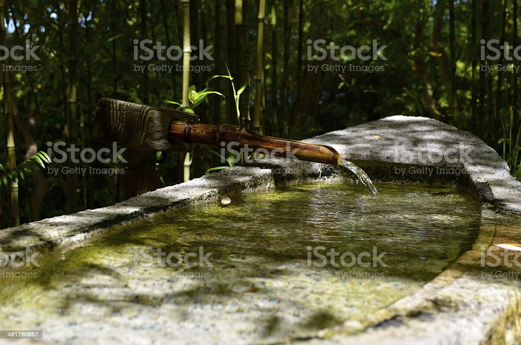 bamboo fountain trickling water into stone trough stock photo
