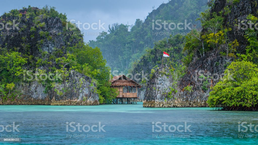 Bamboo Hut between some Rocks under Rain in Bay with Indonesian Flag, Pianemo Islands, Raja Ampat, West Papua, Indonesia - Royalty-free Adventure Stock Photo