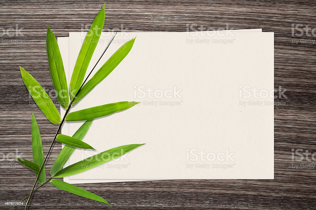 Bamboo leaf and and paper on wood background stock photo