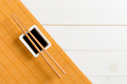 Bamboo mat and soy sauce with sushi chopsticks on white wooden table. Top view with copy space background for sushi. Flat lay