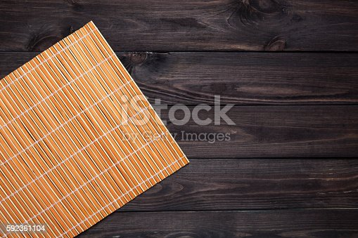 orange bamboo napkin on a dark wooden table, top view