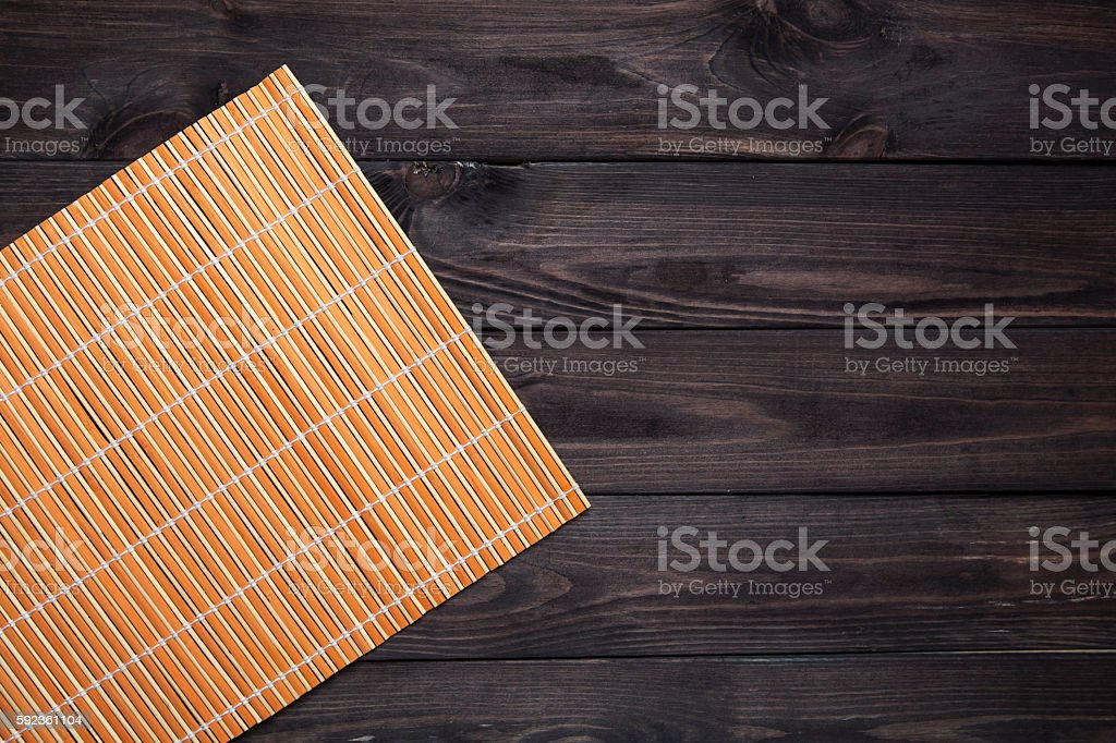 Bamboo mat on wooden table, top view stock photo
