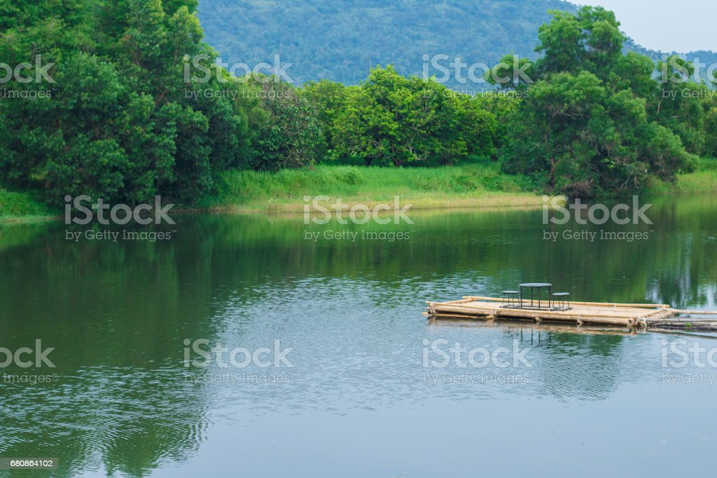 Bamboo raft extending into the water stock photo