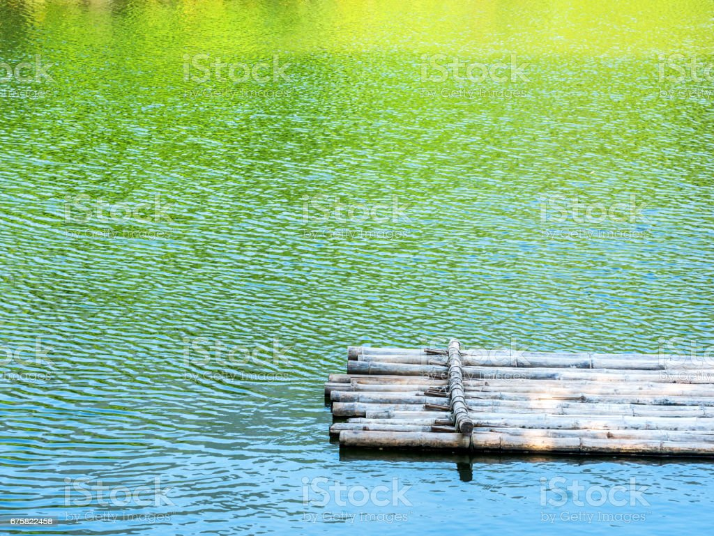 Bamboo raft in river with color reflection of tree,mountain and blue sky in river stock photo