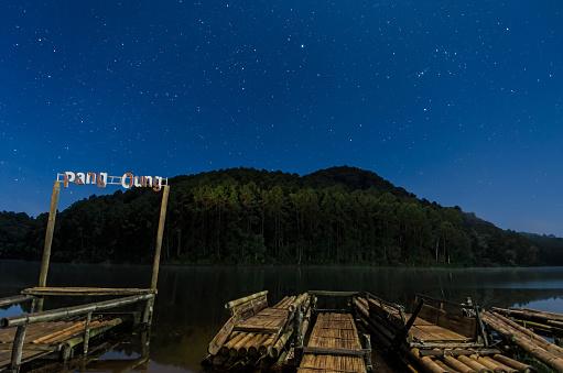 chinese fishermen lighting lantern on bamboo raft on li river