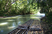 Bamboo rafts prepared & ready for a popular tourist day trip on the Martha Brae river, Falmouth, Jamaica. Close to Montego Bay & Ocho Rios.