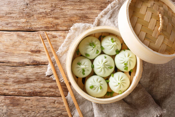 Bamboo steamer with tasty baozi dumplings closeup. Horizontal top view stock photo