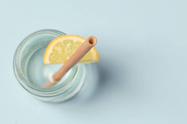 Bambusstroh in einem Glas Zitronenwasser auf blauem Hintergrund, wiederverwendbare Bambusstreifen als Alternative für Einweg-Plastikstreifen, gesundes und nachhaltiges Lifestyle-Konzept – Foto
