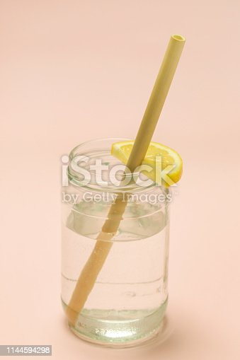 Bamboo straw in a glass of lemon water on the pink background, Reusable bamboo straws as an alternative for single-use plastic straws, healthy and sustainable lifestyle concept