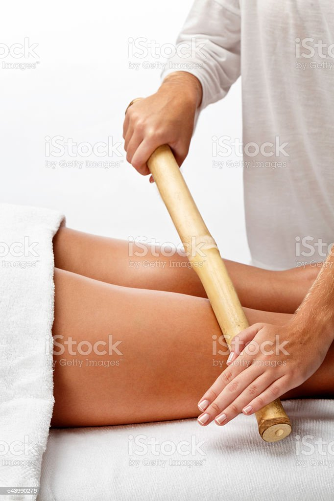 Bamboo therapy massage on legs in Spa stock photo