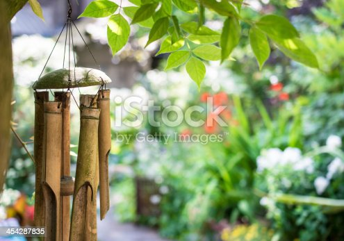bamboo wind chime with garden bokeh in the background and overhanging leafs