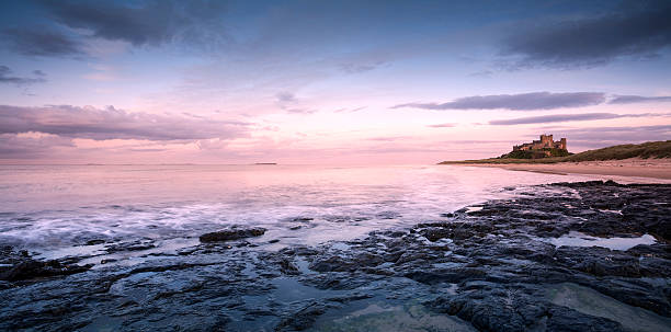 Bamburgh Castle at Sunrise This is Bamburgh Castle in Northumberland, England. The Farne Islands are visible on the horizon. northeastern england stock pictures, royalty-free photos & images