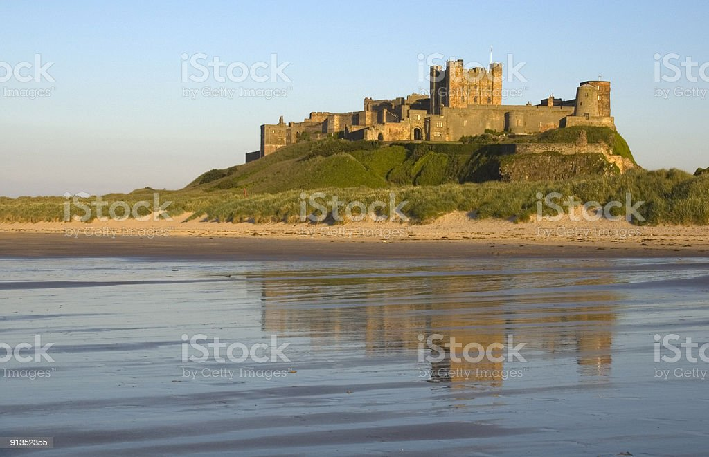 Bamburgh Castle reflects off the water  royalty-free stock photo