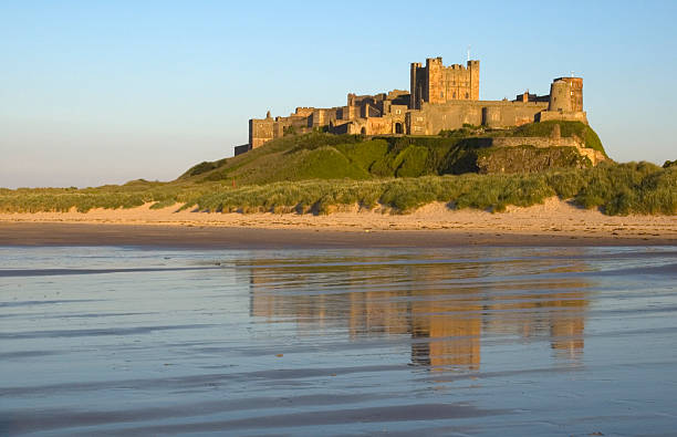 Bamburgh Castle reflects off the water  stock photo