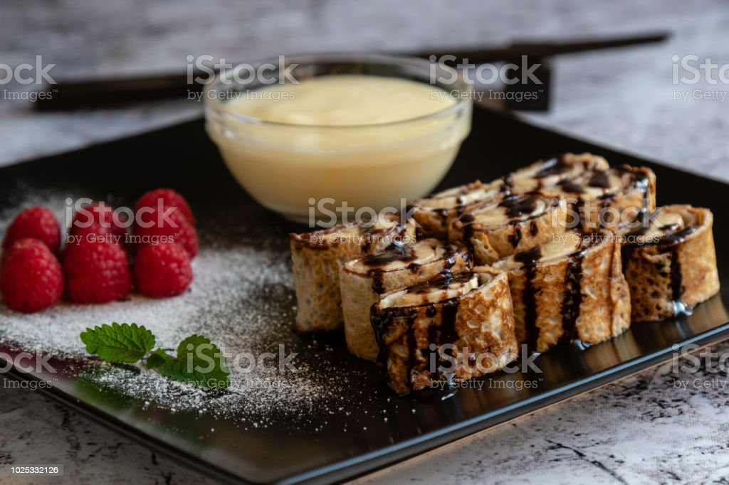 banan pancake sushi dessert with dip and chocolate syrup stock photo