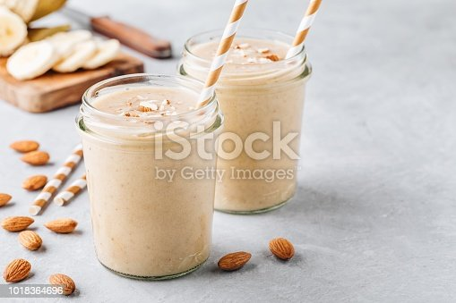 Healthy breakfast. Banana almond smoothie with cinnamon and oat flakes and coconut milk in glass jars