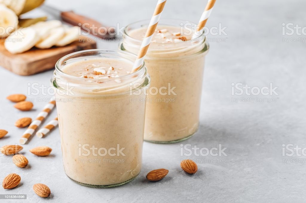 Banana almond smoothie with cinnamon and oat flakes and coconut milk in glass jars stock photo