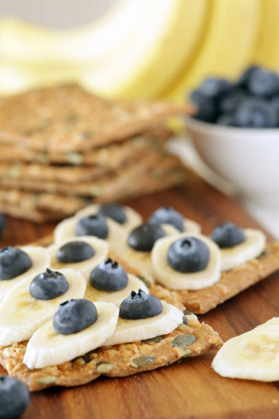 Banana and blueberries on pumpkin seeded crackers - shallow dof stock photo