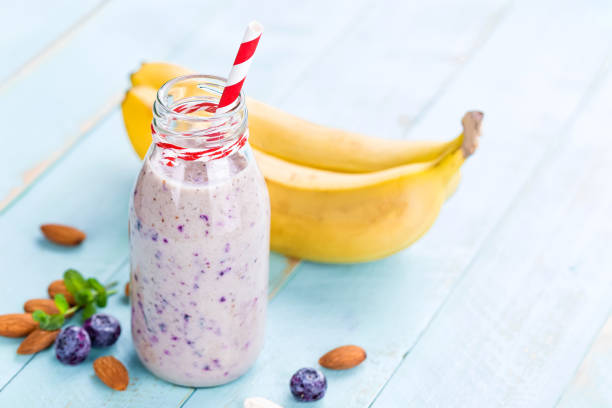 Banana and blueberry diet smoothie with yogurt or milk, almonds and fresh berries in glass bottles, healthy food stock photo