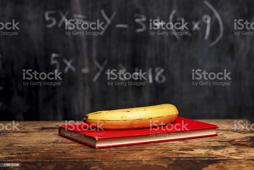 banana and book by blackboard with equation royalty-free stock photo