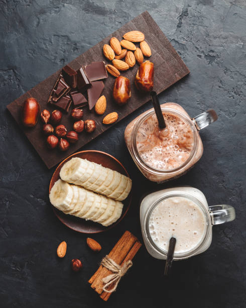 bananen und schokolade smoothie in zwei gläser, protein-milchshake, nüsse, schokolade würfel, bananenscheiben, termine, zimtstangen, gesunde ernährung auf einem dunklen hintergrund, ansicht von oben - kaffee protein shakes stock-fotos und bilder