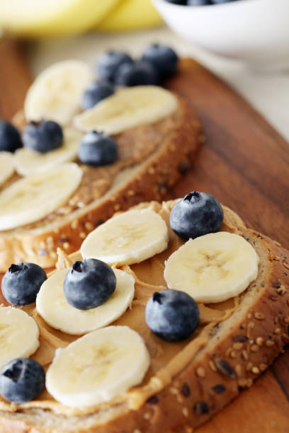Banana, blueberries and peanut butter on wholemeal bagels - shallow dof stock photo