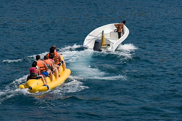 A banana boat being pulled by a boat stock photo