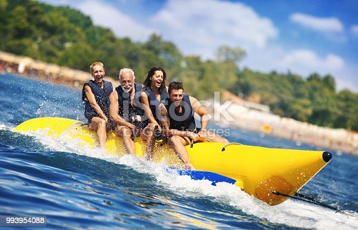 Closeup of senior couple with their children enjoying banana boat ride during their summer vacation. They are excited and hardly holding onto the handles, but it's big fun, especially for the parents.