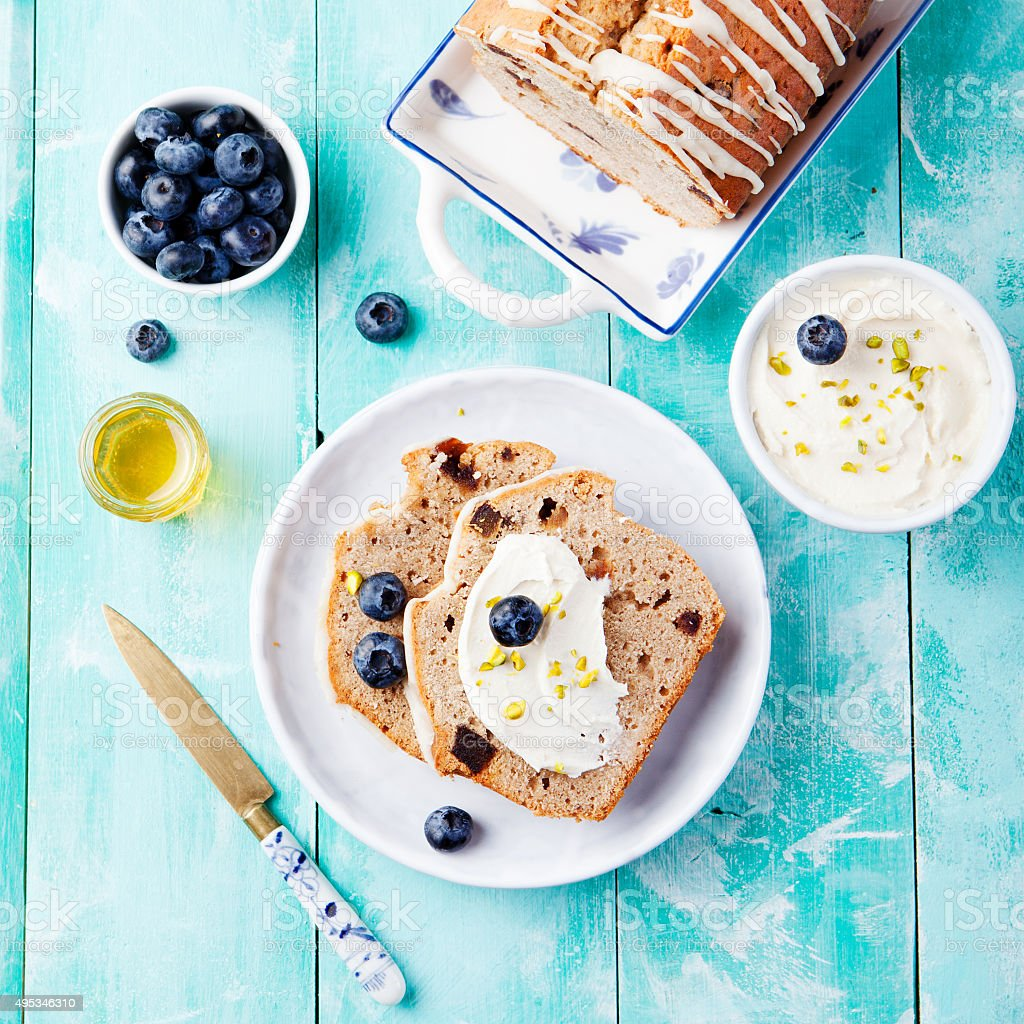 Banana bread with cream cheese frosting, honey, fresh berries blueberries stock photo
