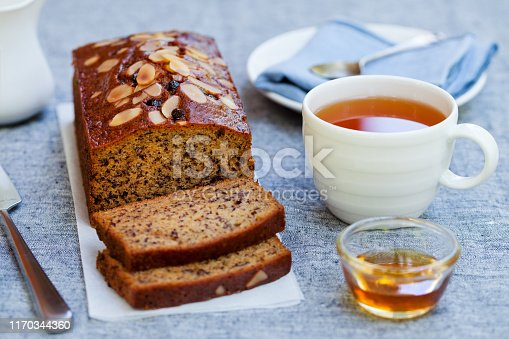 Banana, carrot, apple cake, loaf with chocolate and cup of tea on grey background