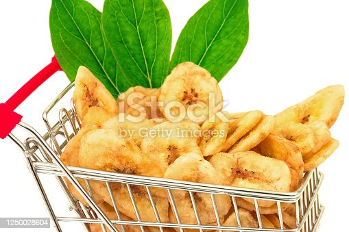 Macro view of banana chips with green leaves in metal trolley on white background
