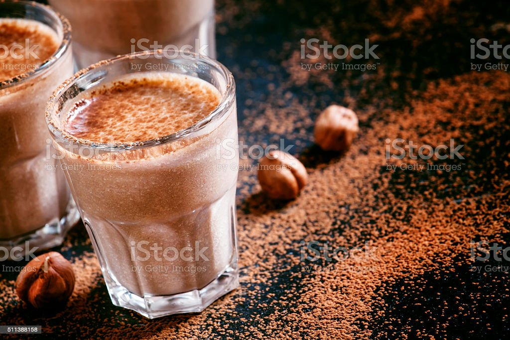 Banana chocolate smoothie with nuts, dusted with a powder stock photo