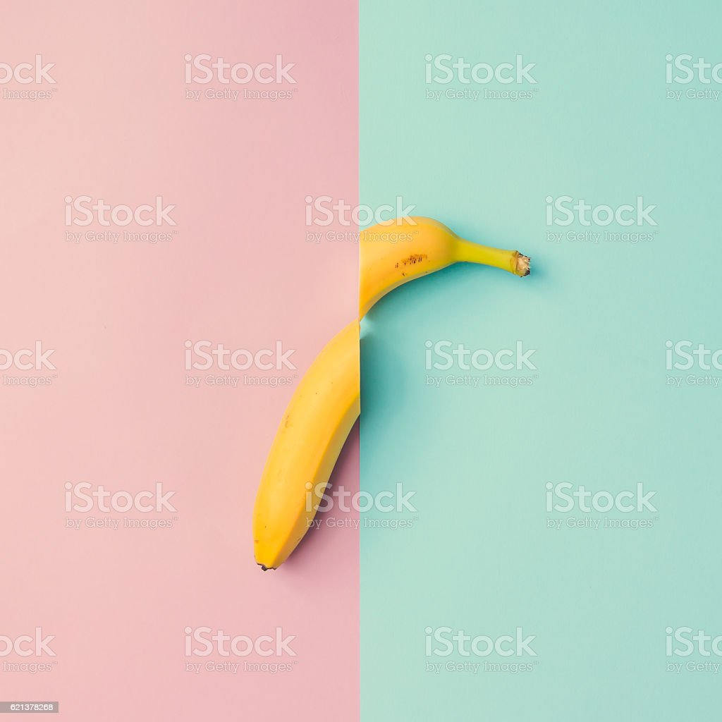 Banana fruit cut in half on pink blue background. stock photo