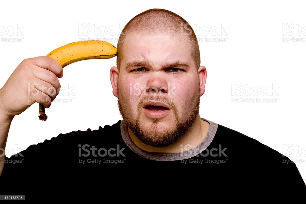 Banana held to head Young man with questioning look holding banana to head. White clipped background. Please vote if you like my images and I'd love to hear how they are used! Adult Stock Photo