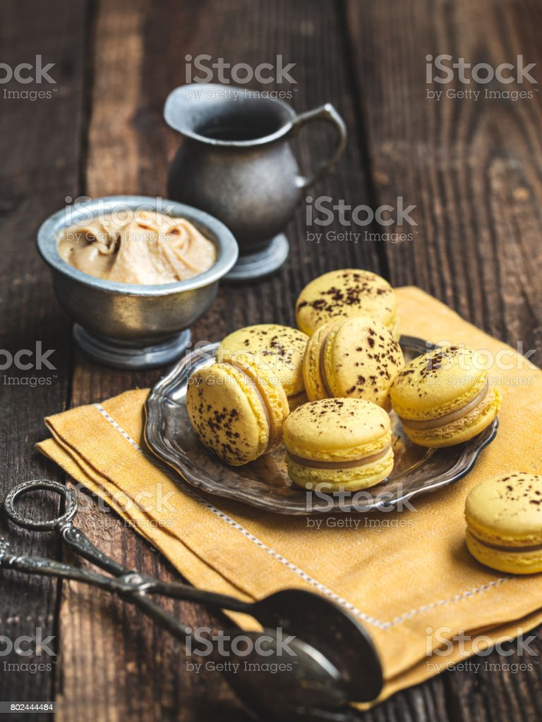 Banana macarons on a rustic wooden table. stock photo