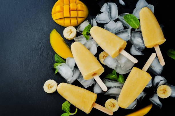 bananen-mango-eis mit früchten und eis - mango eis am stiel stock-fotos und bilder