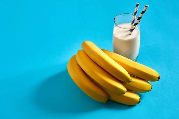 bananen milch trinken und ein paar bananen auf blauem hintergrund - bananeneis stock-fotos und bilder