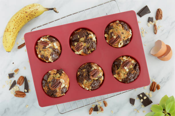 Banana oat pecan chocolate muffins Fresh baked banana oatmeal pecan and chocolate muffins in red silicone muffin pan shot from overhead in natural light.  Healthy and nutritious snack. muffin tin stock pictures, royalty-free photos & images