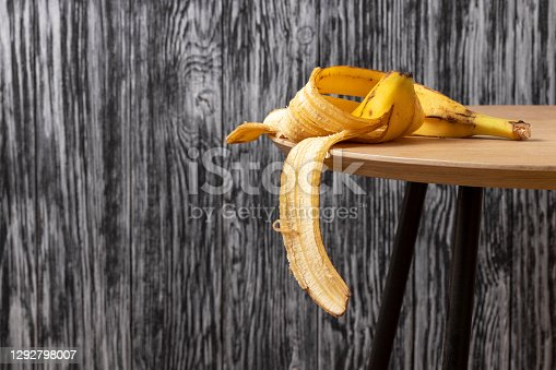 Banana peel on a wooden table. Organic waste concept.